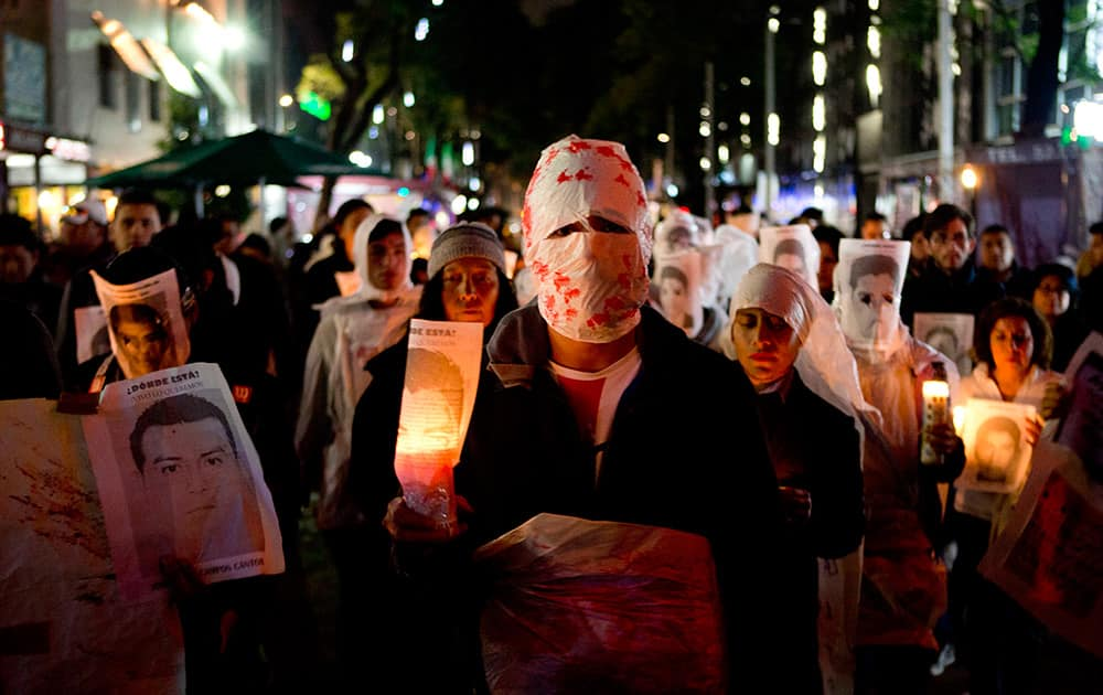 Demonstrators hold candles and images of some of the 43 students who were disappeared, in Mexico City. The 43 teachers-school students disappeared at the hands of a city police force on Sept. 26 in the town of Iguala.