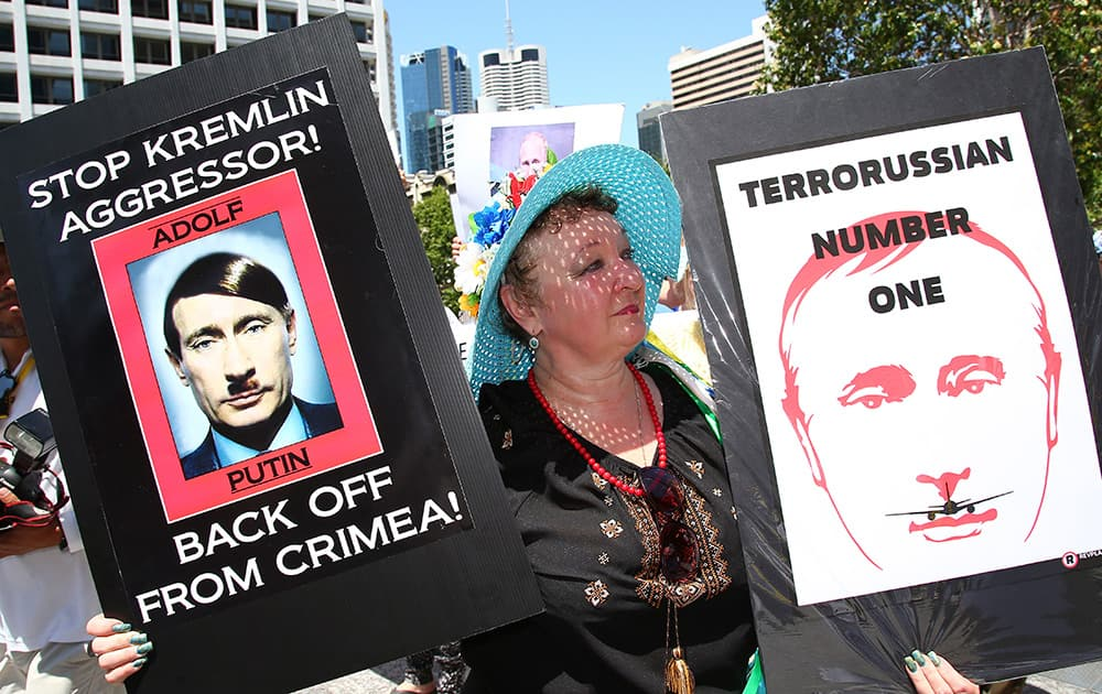 An anti-Russian protester holds placards at a rally during the G-20 in Brisbane, Australia. The protesters staged the rally against the downing of Malaysia Airlines Flight MH17 over eastern Ukraine on July 17 this year.