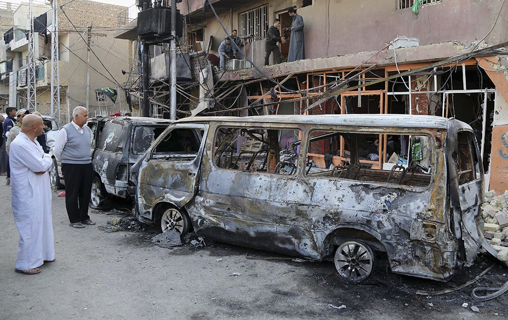 Civilians inspect the site of Friday's car bomb in Baghdad, Iraq. The nighttime blast in the Gorayaat area was the largest of four bombings in and around the city on Friday, mostly targeting Shiite areas.