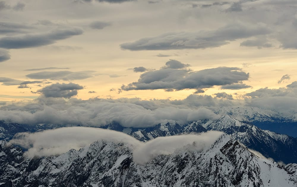 Clouds partly cover the sky above Wetterstein mountains near Garmisch-Partenkirchen, in the German Alps at sunrise.