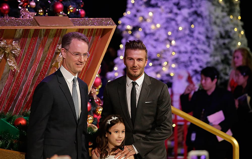 Former England soccer captain David Beckham, is accompanied by Marina Bay Sands President and Chief Executive Officer George Tanasijevich, attends a Christmas tree lighting at the Marina Bay Sands Casino Resorts, in Singapore.
