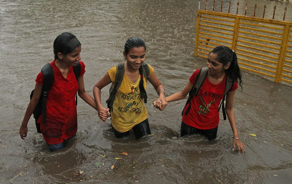 Indian girls hold hands and wade through a waterlogged street caused by unseasonal rainfall in Ahmadabad, India.
