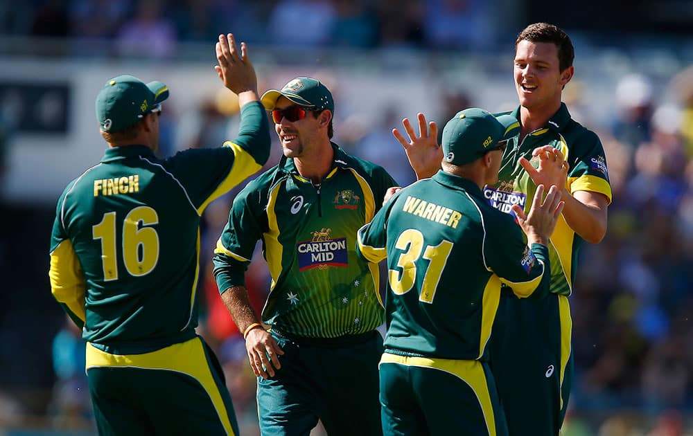 Australia's Josh Hazlewood, right, is congratulated by team mates after taking the wicket of South Africa's Quinton de Kock during their second one-day international cricket match in Perth, Australia.