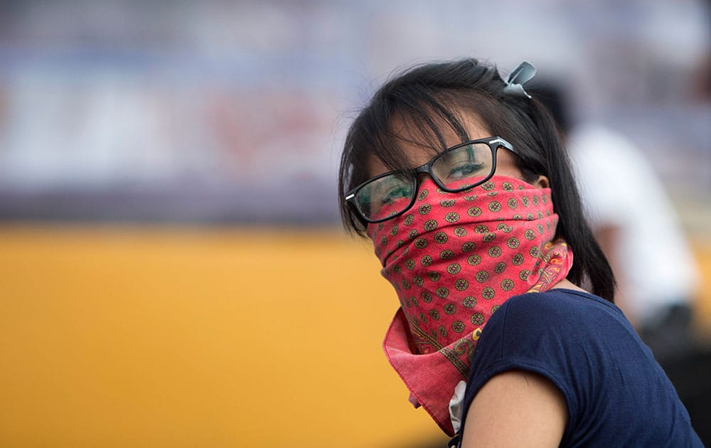 A student with her face covered looks over her shoulder as she marches inside Mexico's National University, UNAM, campus in Mexico City.
