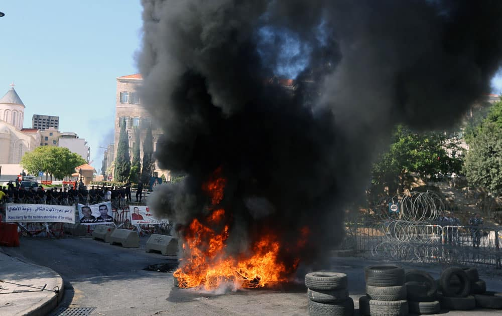 Lebanese riot policemen stand guard, left, while relatives of Lebanese soldiers held hostage by Islamic militants burn tires during a demonstration to demand action to secure the captives' release, in front of government headquarters in downtown Beirut, Lebanon.