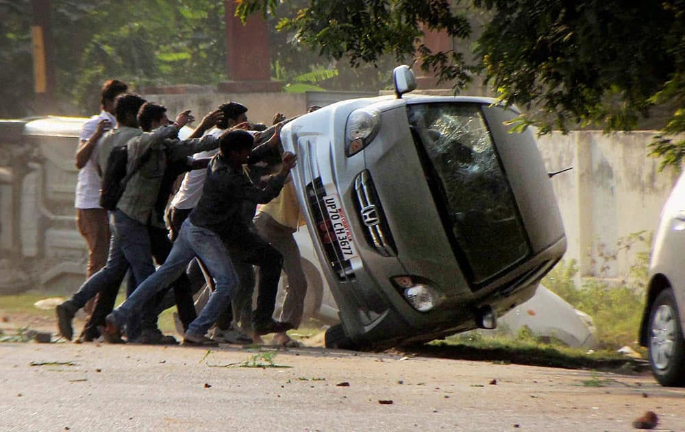 People overturn vehichle of a lawyer during a clash in Allahabad.
