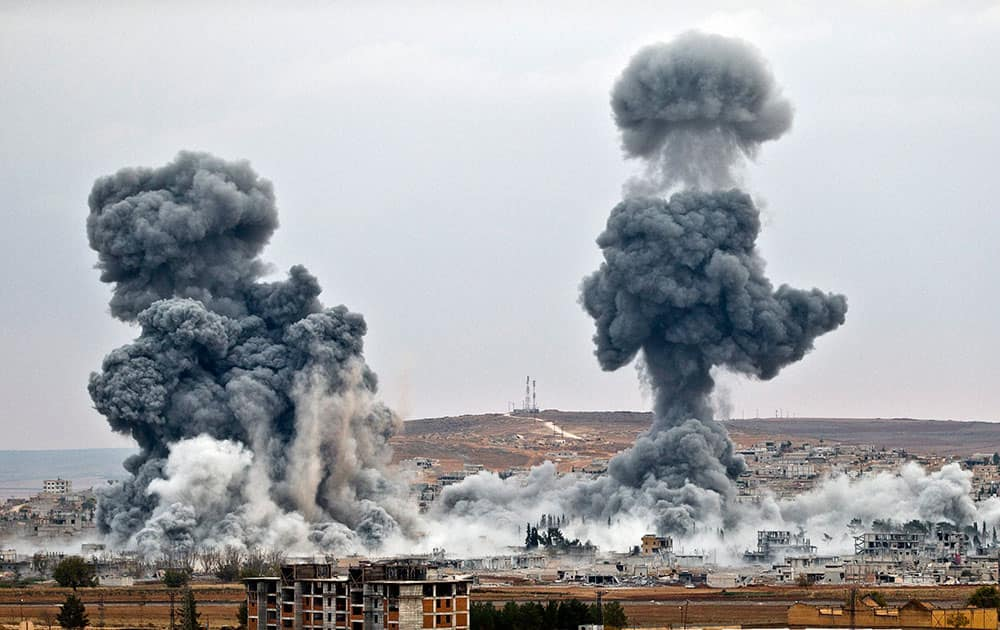 Smoke rises from the Syrian city of Kobani, following airstrikes by the US led coalition, seen from a hilltop outside Suruc, on the Turkey-Syria border.