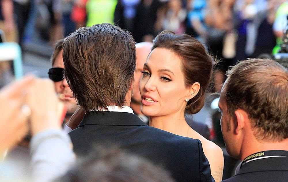 Movie star Angelina Jolie, director of 'Unbroken', speaks with Brad Pitt at the World Premiere of her film in Sydney.
