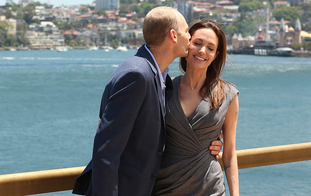 Angelina Jolie, who directed and produced the film 'Unbroken,' receives a kiss from actor Geoff Evans at a photo session after a press conference following the movies world premiere in Sydney.