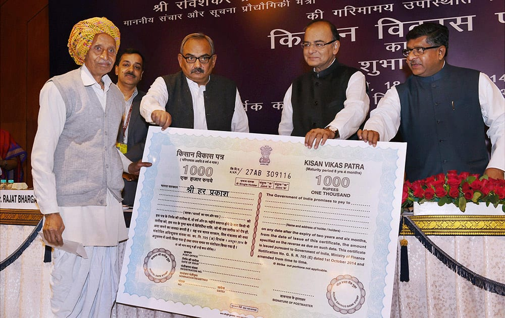 Union Finance Minsiter Arun Jaitley presents first KVP to Harprakash as Union Communications & Information Technology Minister Ravi Shankar Prasad looks on at the launch of the Kisan Vikas Patra (KVP) at a function in New Delhi.