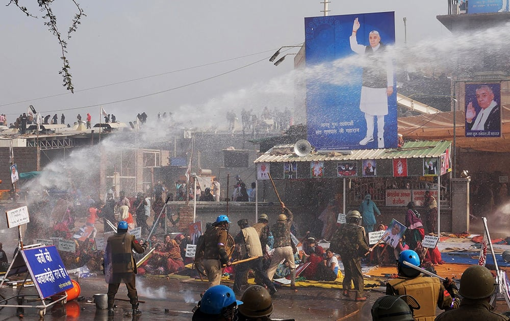 Police use batons and water cannon to disperse supporters, as they storm the ashram of controversial guru Sant Rampal, at Hisar in Haryana.