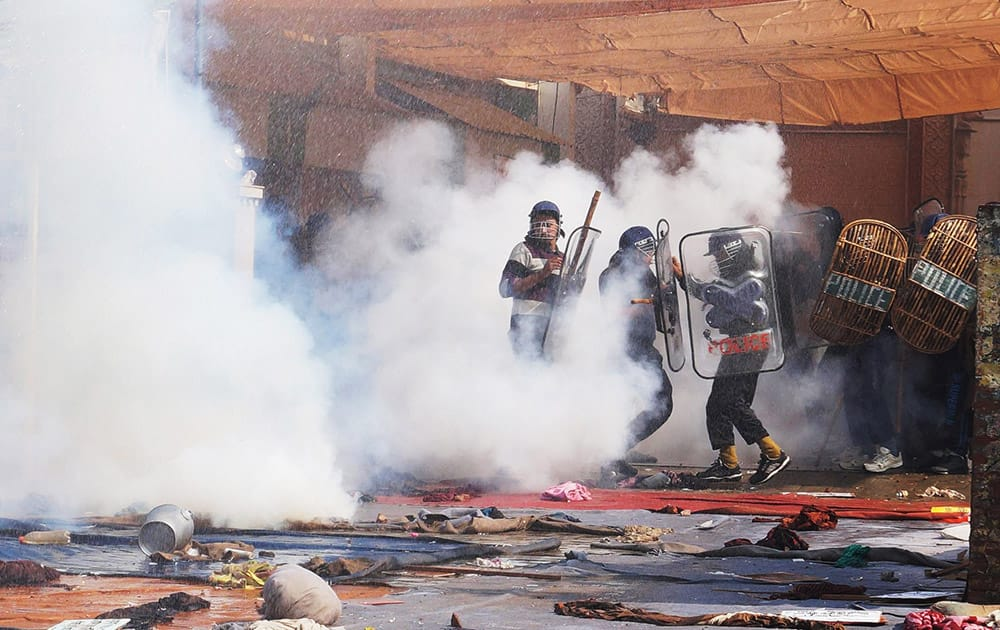 Indian police use tear gas to disperse supporters, as they storm the ashram of controversial Indian guru Sant Rampal, at Hisar in Haryana state.