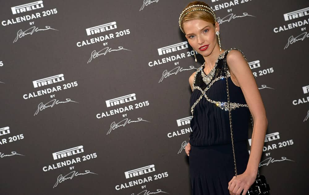 Model Sasha Luss poses for the photographers as she arrives at the Gala Dinner on the occasion of the presentation of the Pirelli 2015 Calendar by Steven Meisel, unveiled in Milan.