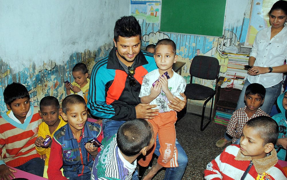 Suresh Raina interacts with kids at a school during a cleanliness drive in Ghaziabad.