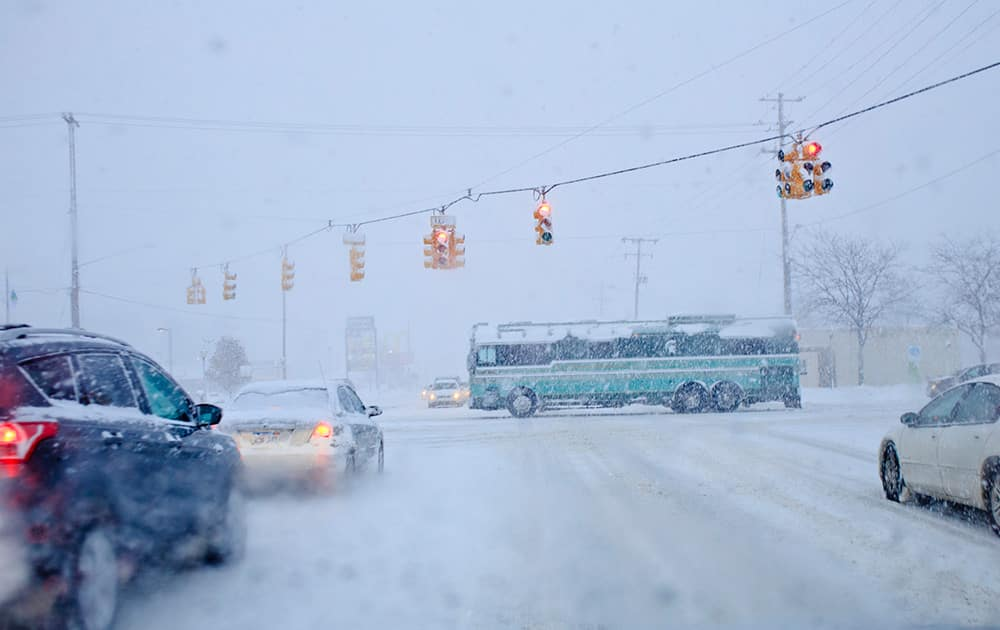 A bus passes through the intersection of Lake Michigan Dr. and Wilson Ave. in Walker, Mich. Lake-effect storms in Michigan produced gale-force winds and as much as 18 inches of snow, and canceled several flights at the Grand Rapids airport.