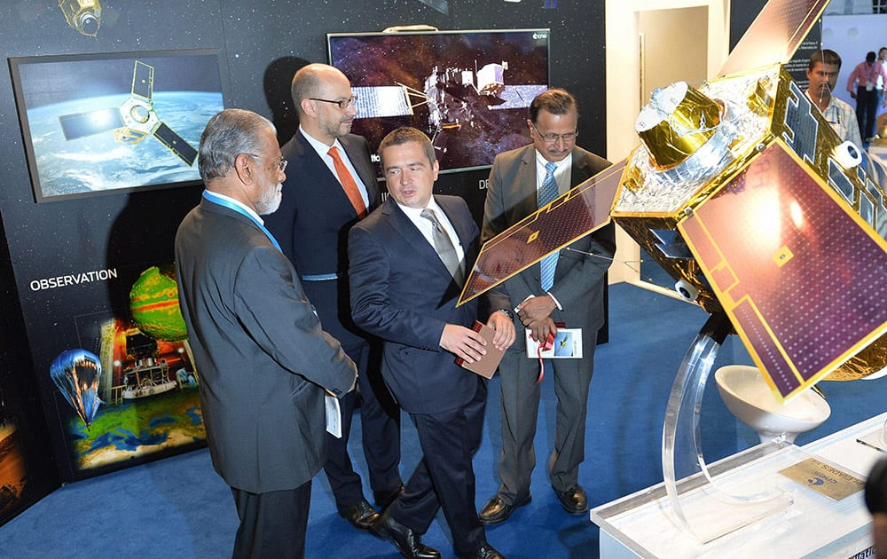 Managing Director, French Space Agency Liason Office and Diplomat at Embassy of France in Bangalore, Mathieu J. Weiss (2L) points to a scaled down model of Pleiades-HR (High-Resolution Optical Imaging Constellation), one of the two-spacecraft constellation of CNES (Centre National dEtudes Spatiales), the Space Agency of France, at a stall during the 4th edition of Bengaluru Space Expo-2014 in Bengaluru.