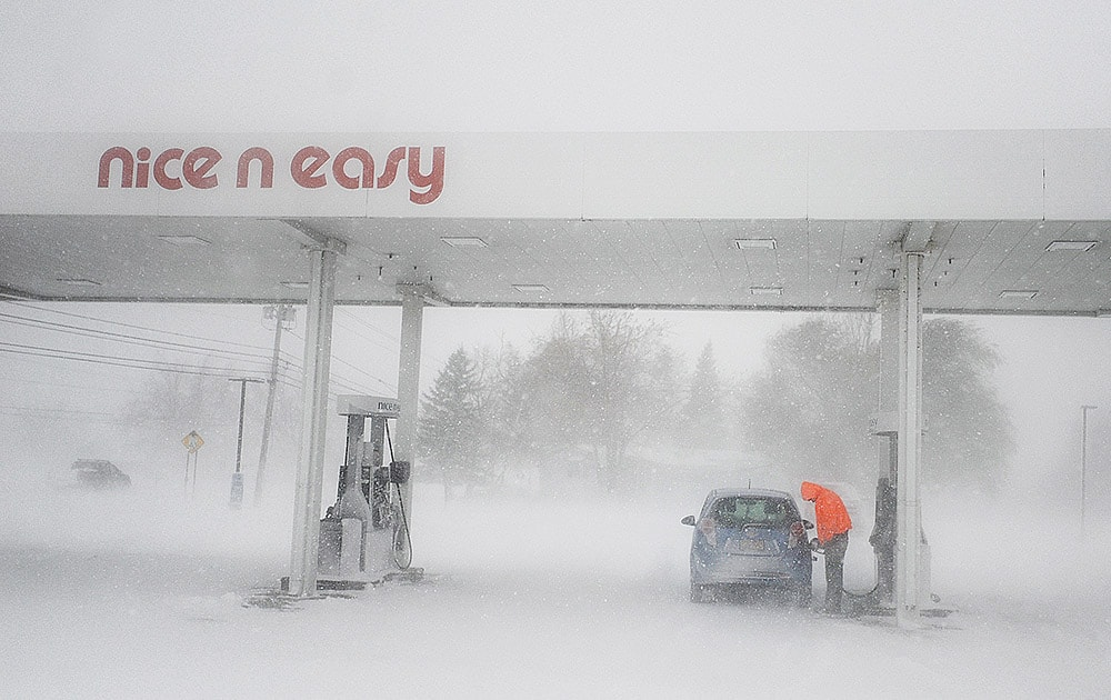A man puts gas in his tank as snow falls at a gas station on New York State Route 12F near Brownville, N.Y. A ferocious lake-effect storm left the Buffalo area buried under 6 feet of snow, trapping people on highways and in homes, and another storm expected to drop 2 to 3 feet more was on its way.