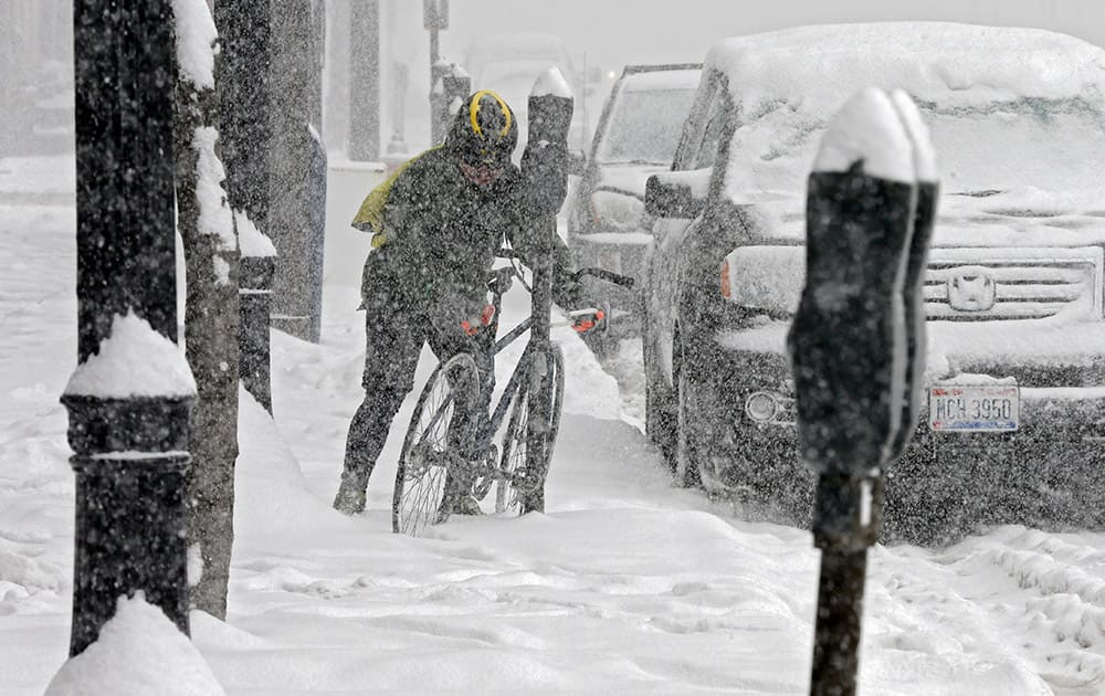 A bicycle messenger chains his bike to a snow-covered parking meter in downtown Cleveland.
