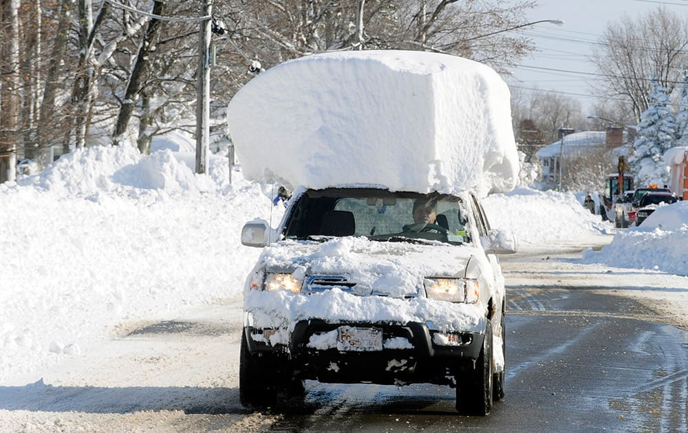 A vehicle, with a large chunk of snow on its top, drives along Route 20 after digging out after a massive snow fall in Lancaster, New York.