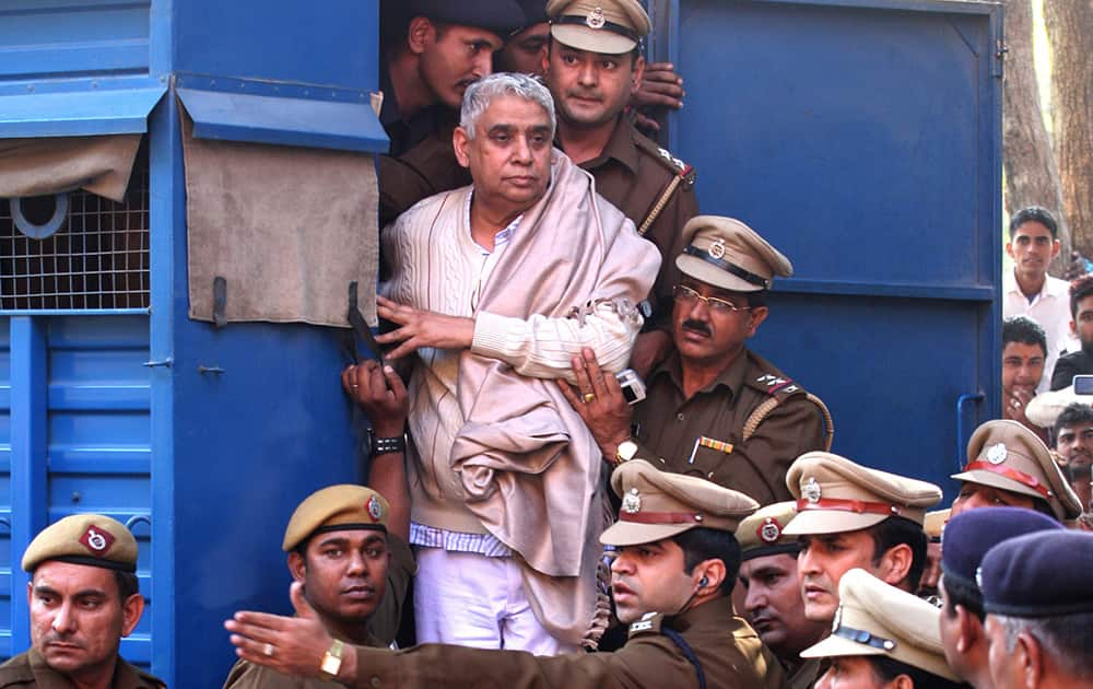 Controversial religious leader Sant Rampal stands by the door of a police van as he is brought to a court, surrounded by police personnel in Chandigarh.