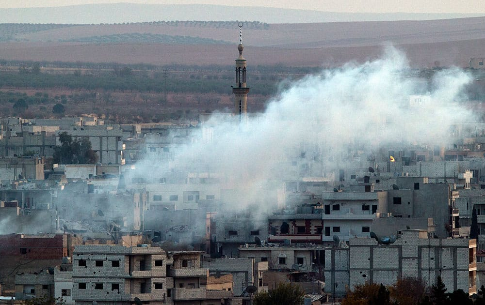 A minaret in Kobani is partly obscured by smoke after a mortar strike during fighting between Islamic state group forces and Kurdish fighters, seen from a hill outside Suruc, on the Turkey-Syria border.
