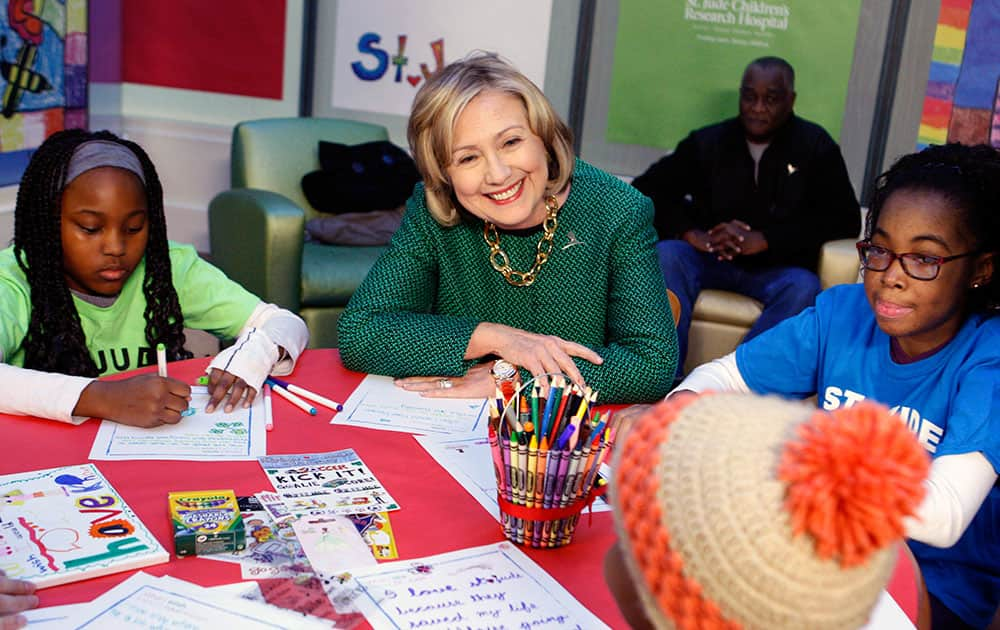 Former Secretary of State Hillary Rodham Clinton, flanked by Adriana Chaney and Carrie-Lynn Grazette, meets with St. Jude children in a clinic before the dedication of The Marlo Thomas Center for Global Education & Collaboration at St. Jude Children's Research Hospital.