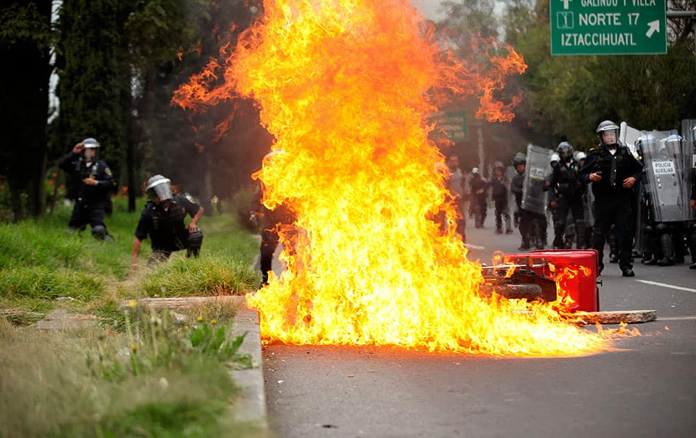 A motorcycle burns after protesters threw molotov cocktails at riot police near the airport in Mexico City.