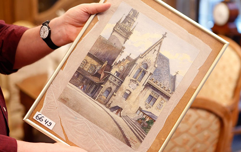 """A picture titled """"The Old City Hall"""" that - as the auction house said - was painted by Adolf Hitler is displayed in an auction house in Nuremberg, Germany. The 100-year-old watercolor of Munich's city hall is expected to fetch at least 50,000 euros (US$ 60,000) at auction this weekend, not so much for its artistic value as for the signature in the bottom left corner: A. Hitler."""