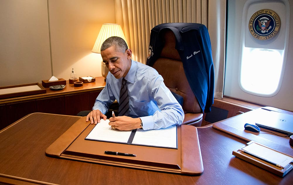 President Barack Obama signs two presidential memoranda associated with his actions on immigration in his office, on Air Force One as he arrives at McCarran International Airport in Las Vegas.