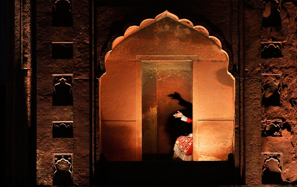 A young Indian Muslim girl, attending the anointment ceremony of Syed Shaban Bukhari, makes hand shadow puppets on a wall of the Jama Masjid in New Delhi, India.