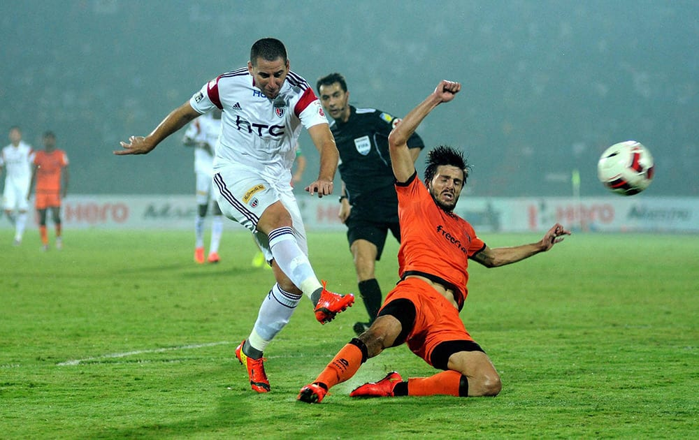 Players of North East United FC (in white) and Delhi Dynamos FC (in orange) in action during their ISL match, at Indira Gandhi Stadium in Guwahati.