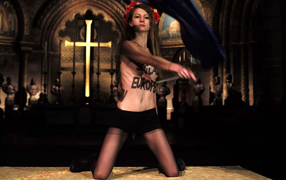 A member of the Ukrainian feminist protest group FEMEN, waves the European Union flag, as she stages a protest inside the cathedral of Strasbourg, eastern France.
