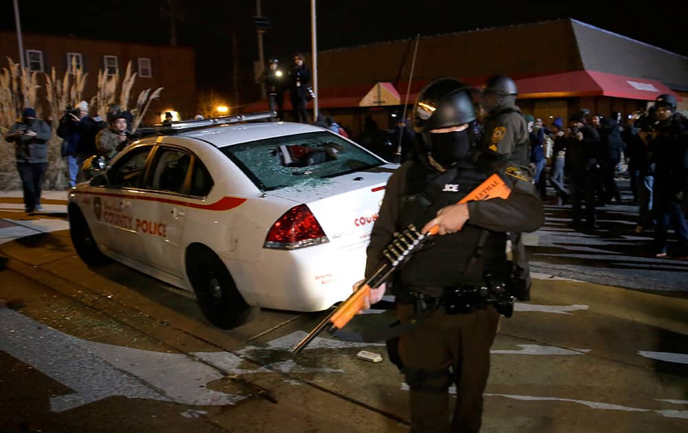 An armed police officer guards the area after a group of protesters vandalize a police cruiser after the announcement of the grand jury decision not to indict police officer Darren Wilson in the fatal shooting of Michael Brown, in Ferguson.
