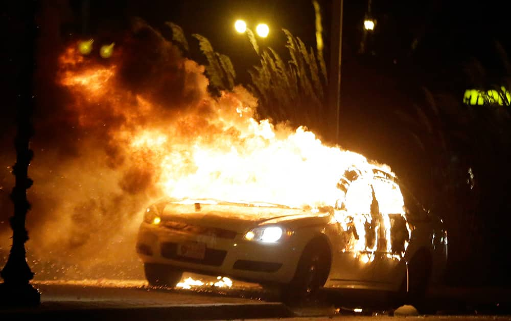A police car is set on fire after a group of protesters vandalize the vehicle after the announcement of the grand jury decision, in Ferguson.