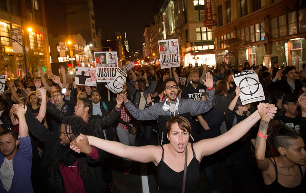 Protestors clasp hands as they march up Seventh Avenue towards Times Square after the announcement of the grand jury decision not to indict police officer Darren Wilson in the fatal shooting of Michael Brown, in New York.