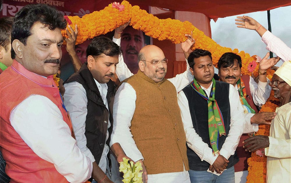 BJP NATIONAL PRESIDENT AMIT SHAH IS GARLANDED AT AN ELECTION RALLY IN BUNDU NEAR RANCHI.