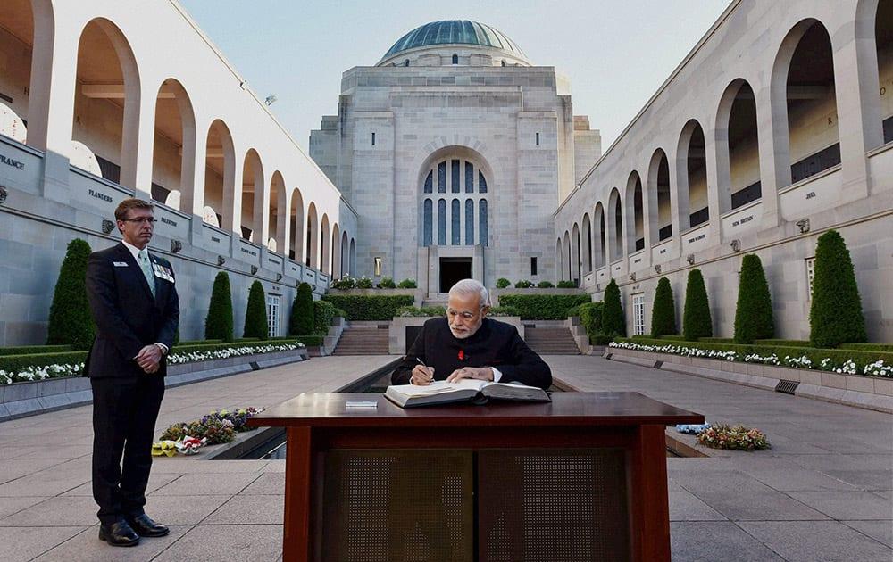 PRIME MINISTER NARENDRA MODI SIGNS VISITORS BOOK DURING A VISIT TO AUSTRALIAN WAR MEMORIAL.