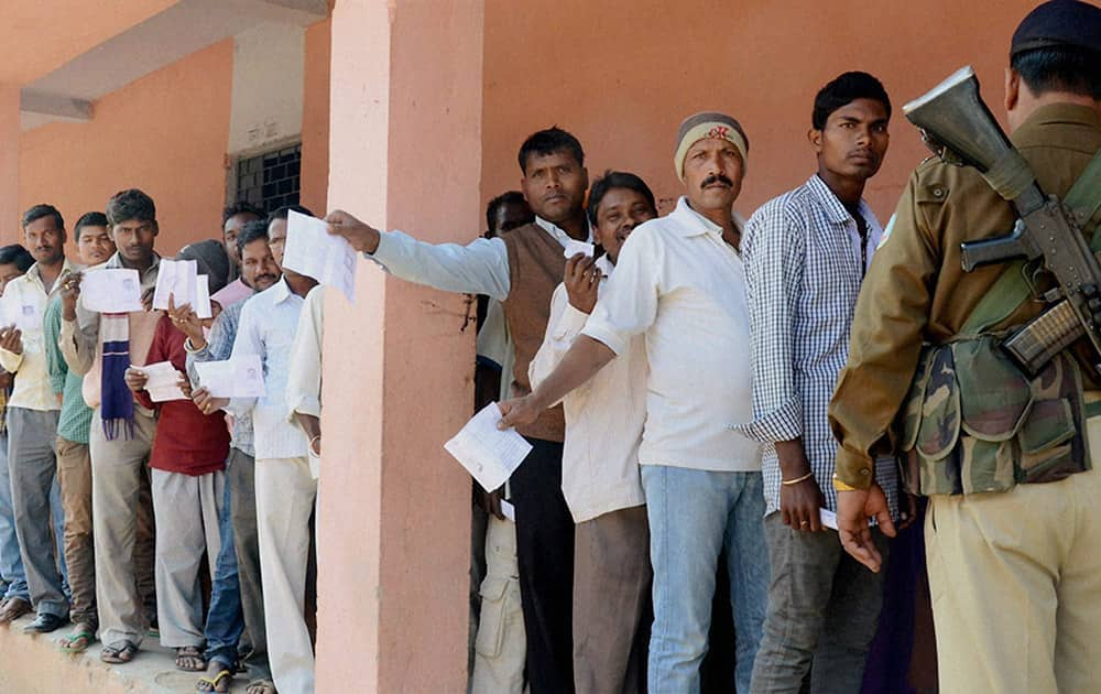 People queue up to cast their vote for Assembly elections at a polling station in Daltonganj in Jharkhand.