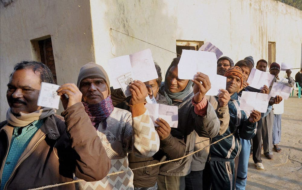 Voters wait to cast their votes during the first phase of Jharkhand assembly elections at a polling station in Lohardaga.