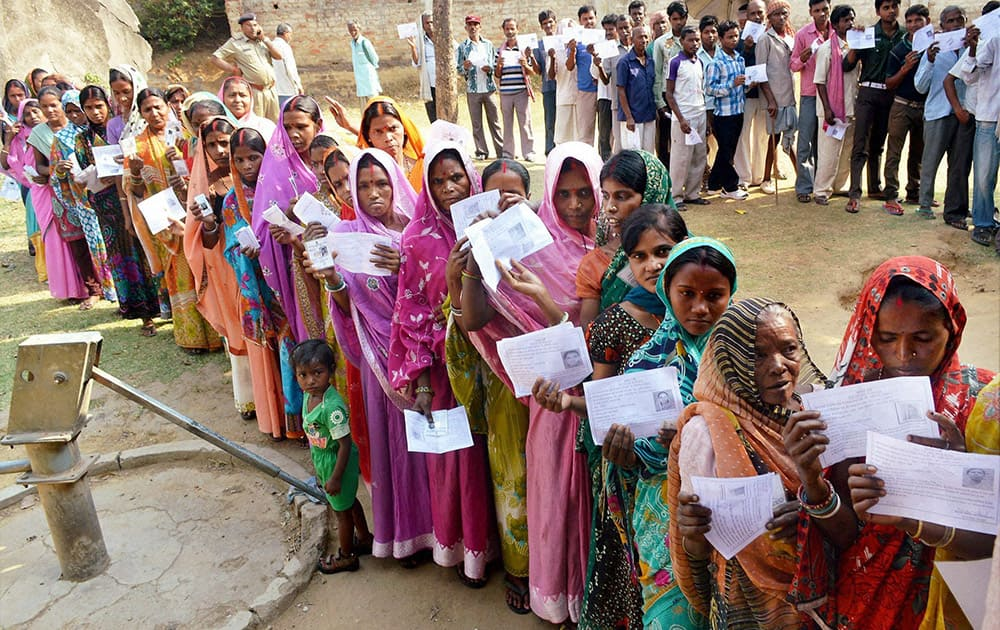 Women display their identity cards while waiting to cast their vote during the first phase of Assembly elections in Chatra district of Jharkhand.