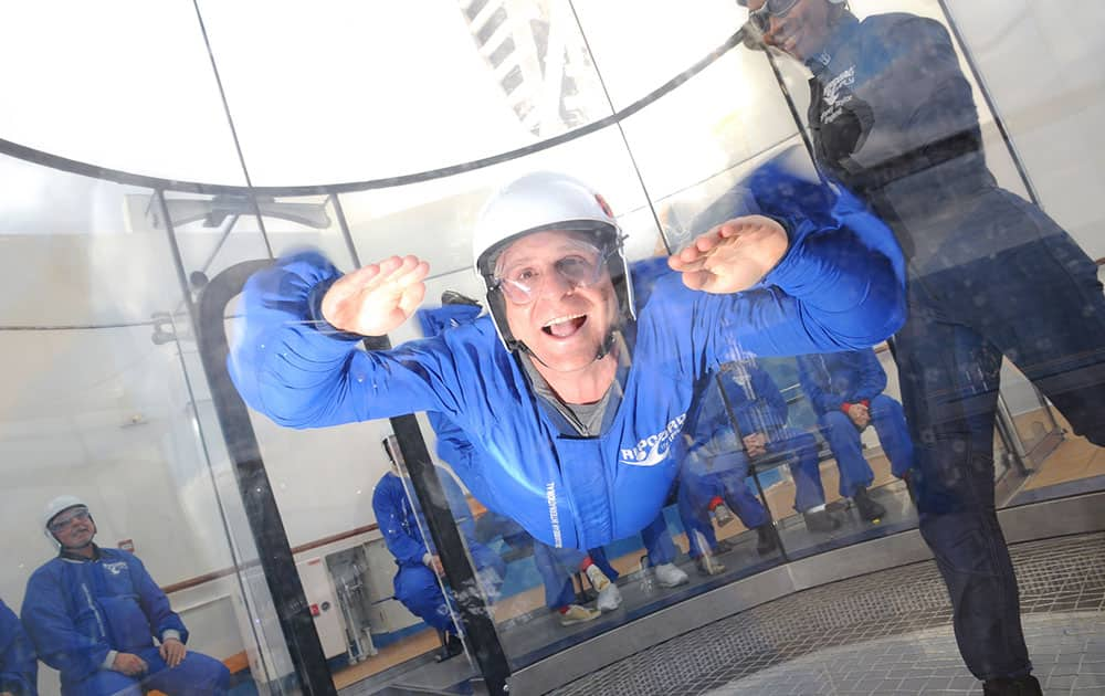 Scott Mayerowitz in the skydiving simulator aboard Royal Caribbean's new Quantum of the Seas ship. Participants don special uniforms, earplugs, goggles and helmets, and float in the air on gusts from a powerful fan inside a giant wind tunnel. Instructors coach participants on how to move inside the tube.