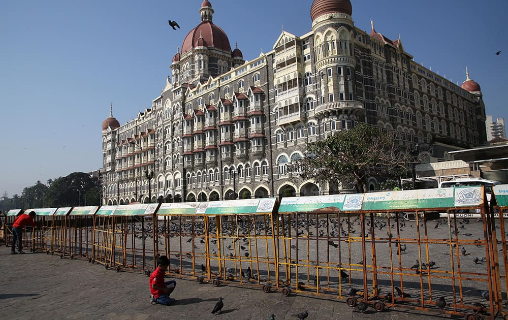 A boy feeds pigeons in front of the Taj Mahal Hotel, one of the sites of the Mumbai terror attack, on the sixth anniversary of the attack in Mumbai.