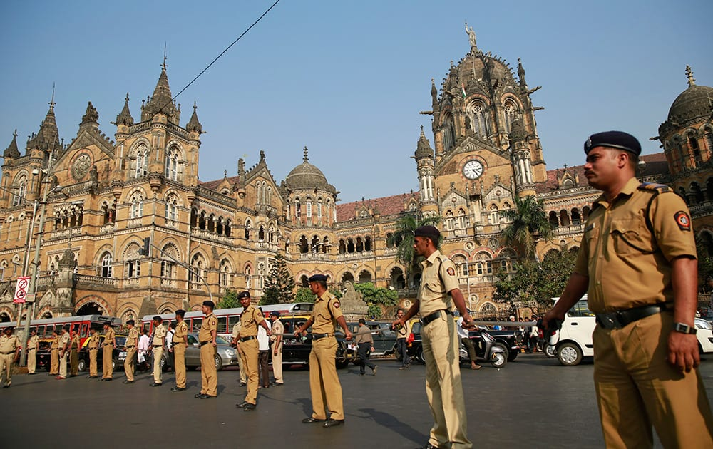 Policemen stand guard outside the Chhatrapati Shivaji train station, one of the sites of the 2008 terror attack, in Mumbai.
