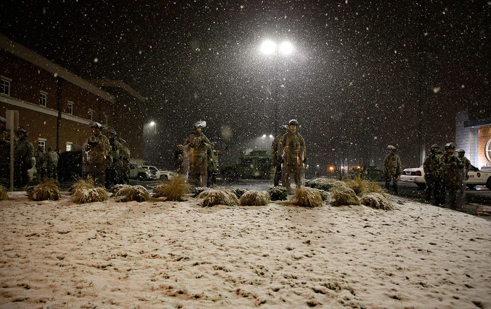 Snow falls as Missouri National Guard stand outside of the Ferguson Police Department in Ferguson, Mo.