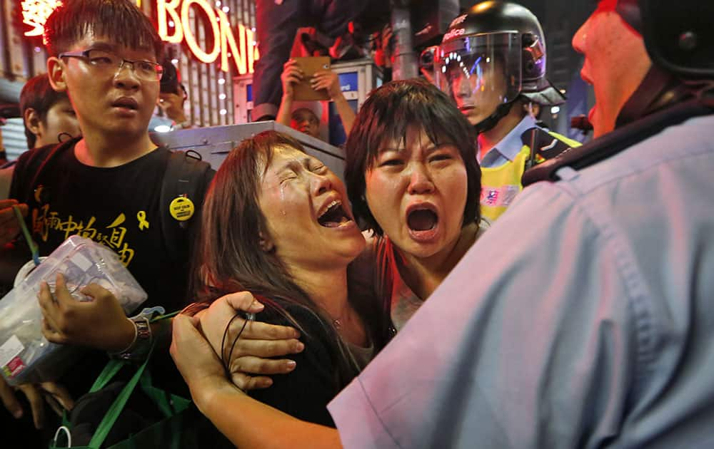 Protesters cry as the police officers try to stop them blocking the road in Mong Kok district of Hong Kong.