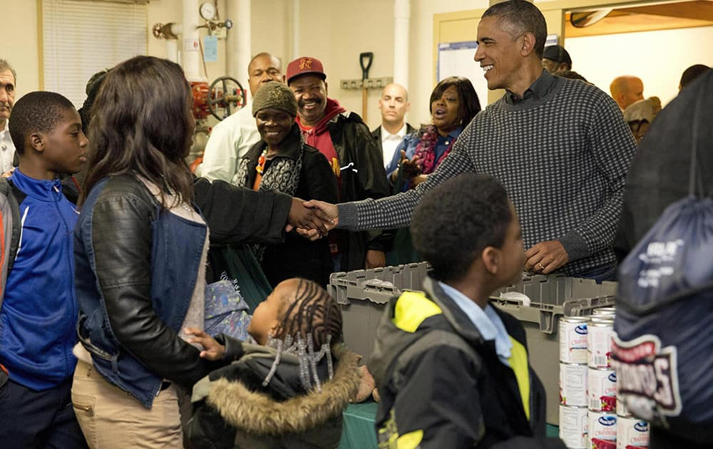President Barack Obama shakes hands with a parton as he and his family distribute food at Bread For The City, in Washington, as part of an annual Thanksgiving tradition of participation in a service event.