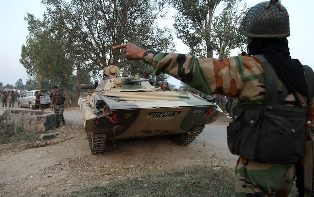 Indian army soldiers arrive in a tank during a gunbattle with armed militants at Pindi Khattar village in Arnia border sector, about 43 kilometers (27 miles) south of Jammu.
