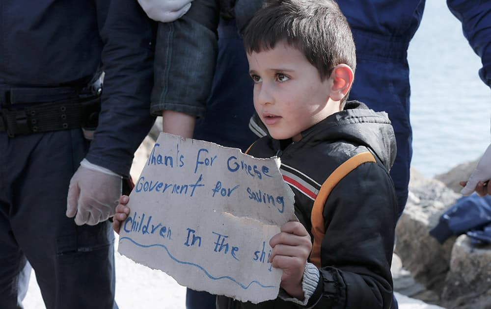 A young boy holds a paper just after disembarking from a crippled freighter carrying hundreds of refugees trying to migrate to Europe, at the coastal Cretan port of Ierapetra, Greece.