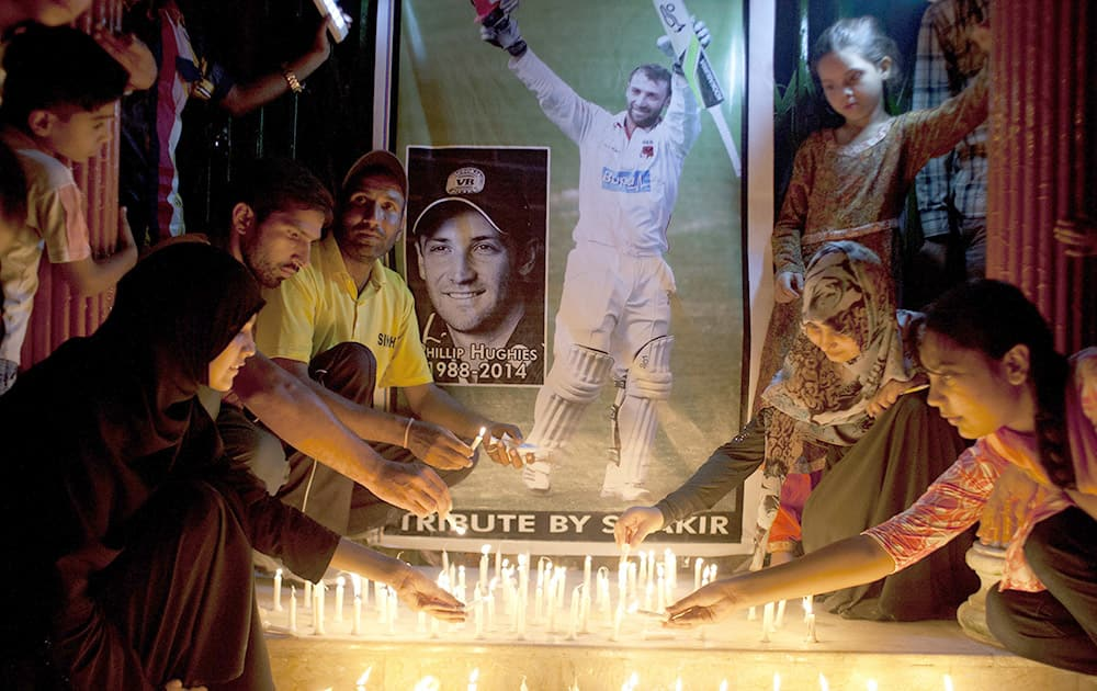 Pakistani cricket fans light candles to pay tribute to Australian cricketer Phillip Hughes in Karachi, Pakistan.