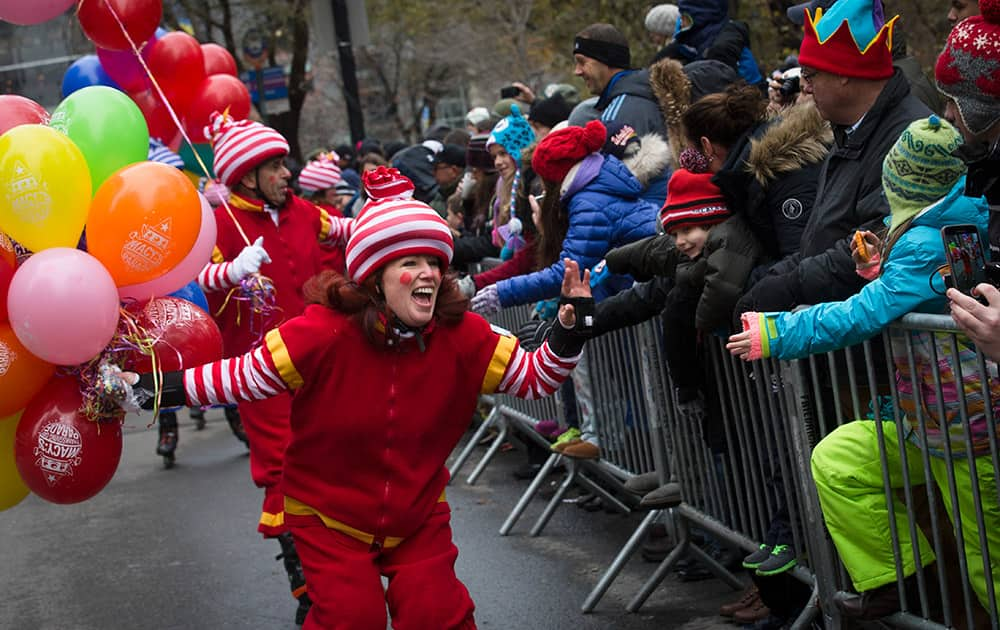 A performer cheers as she skates by spectators during the Macy's Thanksgiving Day Parade, in New York.